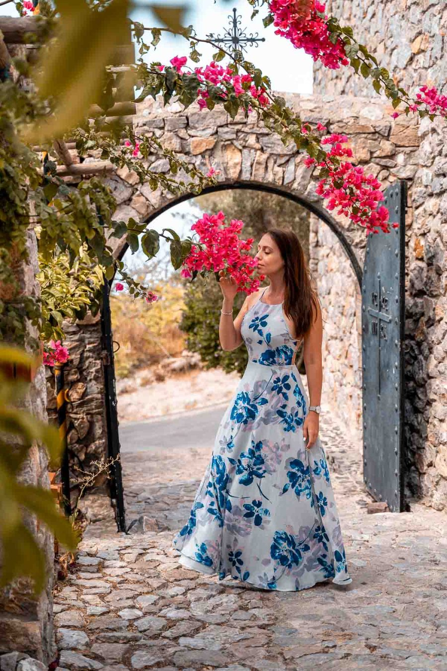 Girl in a blue floral dress smelling the bougainvillea at the Monastery in Santorini