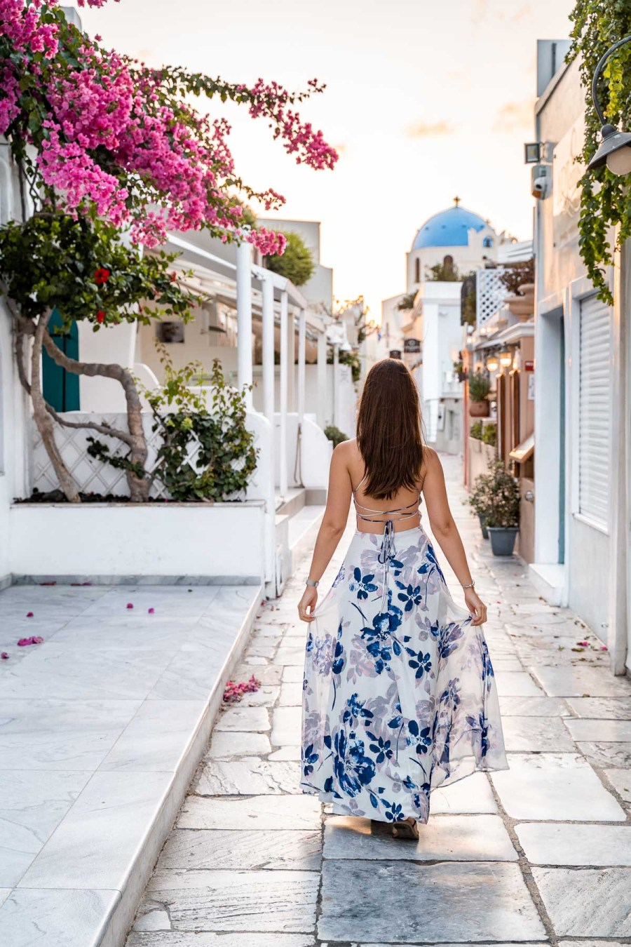 Girl in a blue floral dress standing on the main street of Oia, watching the sunrise