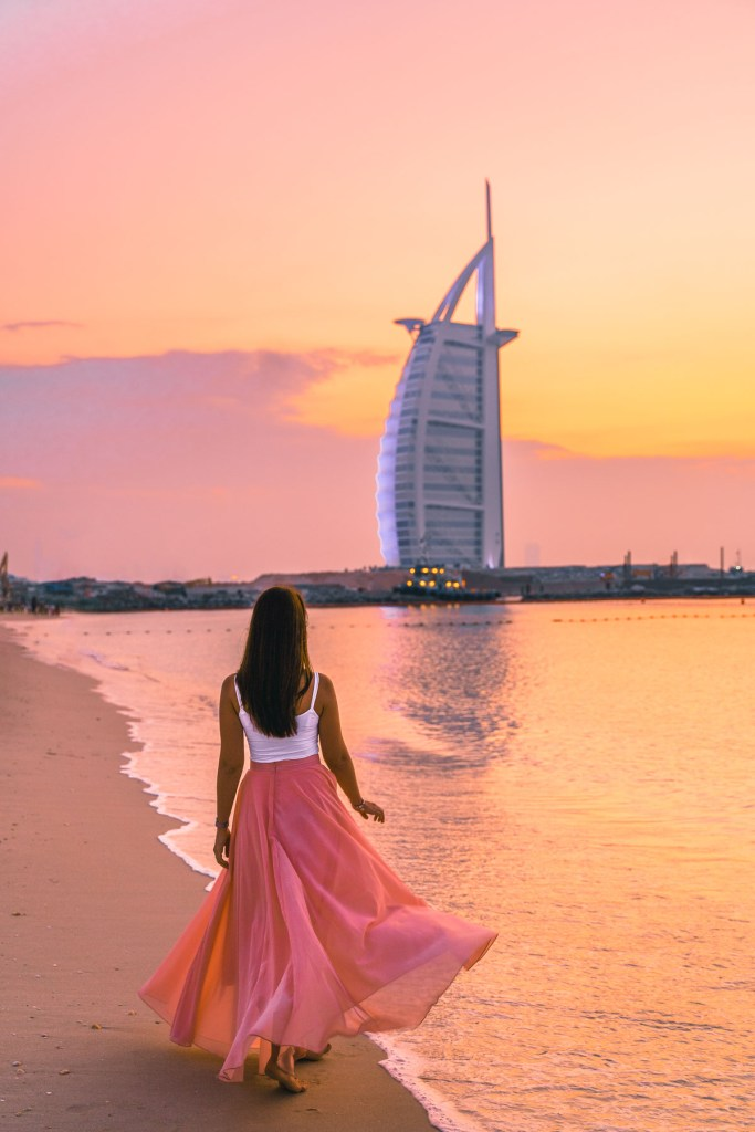 Girl in a flowy pink dress walking at the Jumeirah Beach at sunset with the Burj al Arab in the background