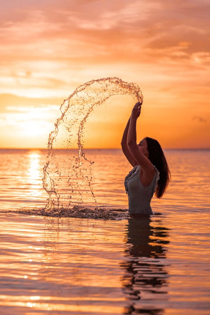 Girl throwing water up in the air in the ocean at sunset in Siquijor, Philippines