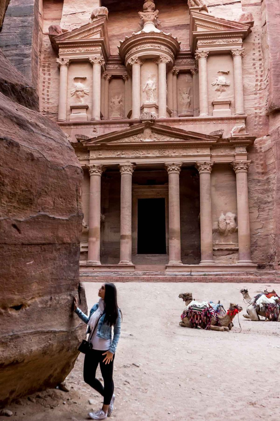 Girl in a denim jacket and jeans standing in front of the Treasury in Petra, Jordan