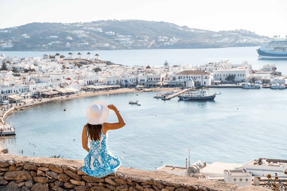 Girl in a blue dress sitting on a wall with the view of Mykonos Town in the background