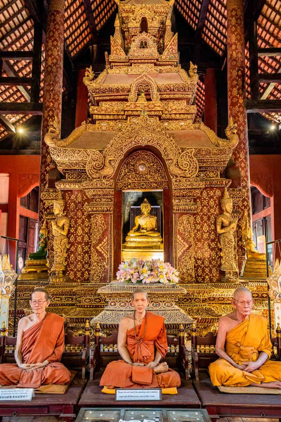 Monks made of vax sitting in front of a Buddha statue in Wat Phra Singh Temple in Chiang Mai
