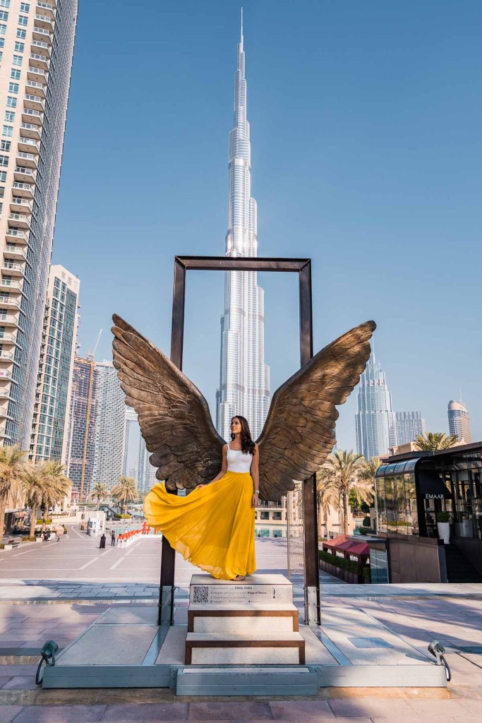 Girl in yellow skirt doing a skirt flip in front of the Wings of Mexico in Dubai with the Burj Khalifa in the background