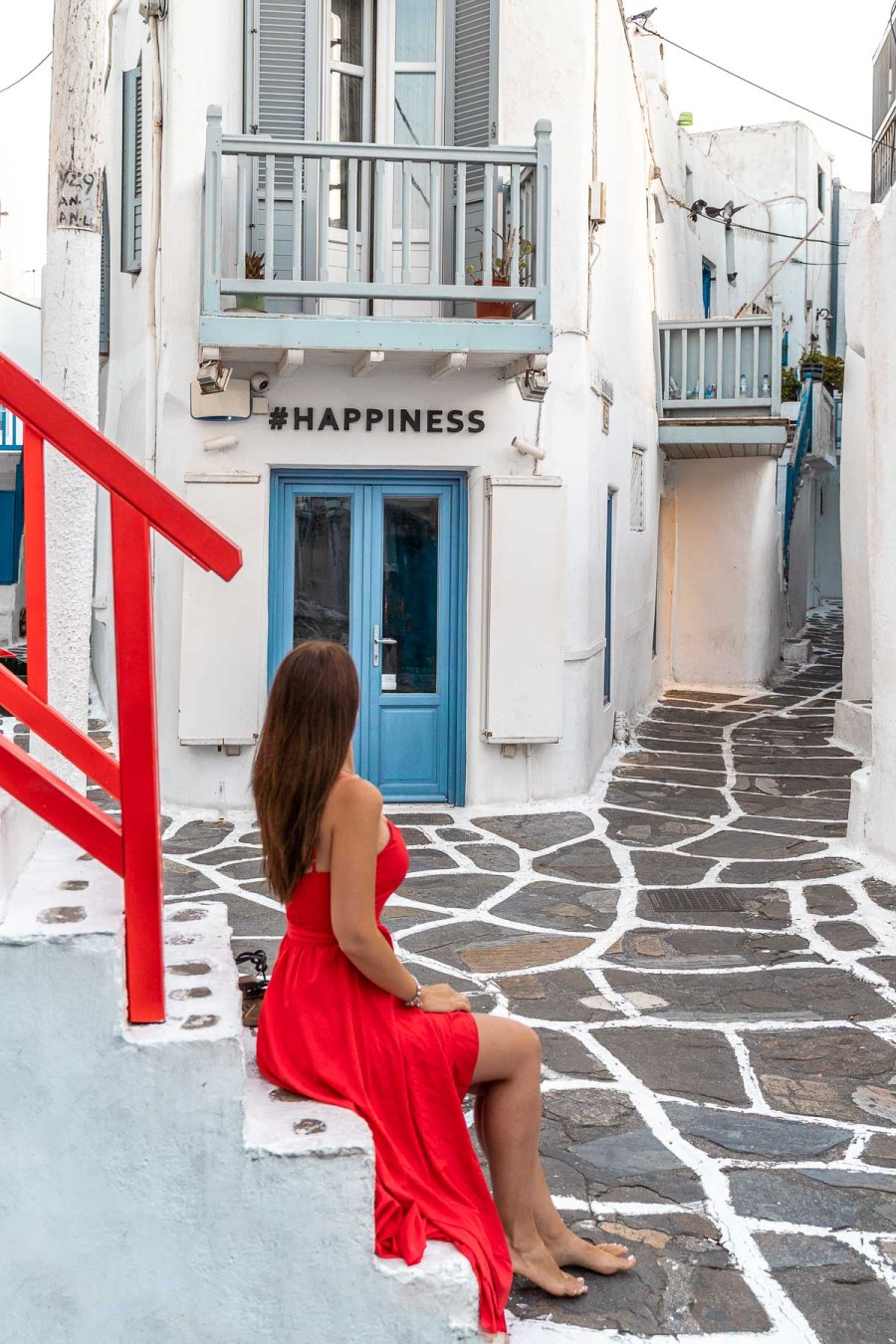 Girl in a red dress sitting on the stairs in front of the #happiness store which is one of the most instagrammable places in Mykonos