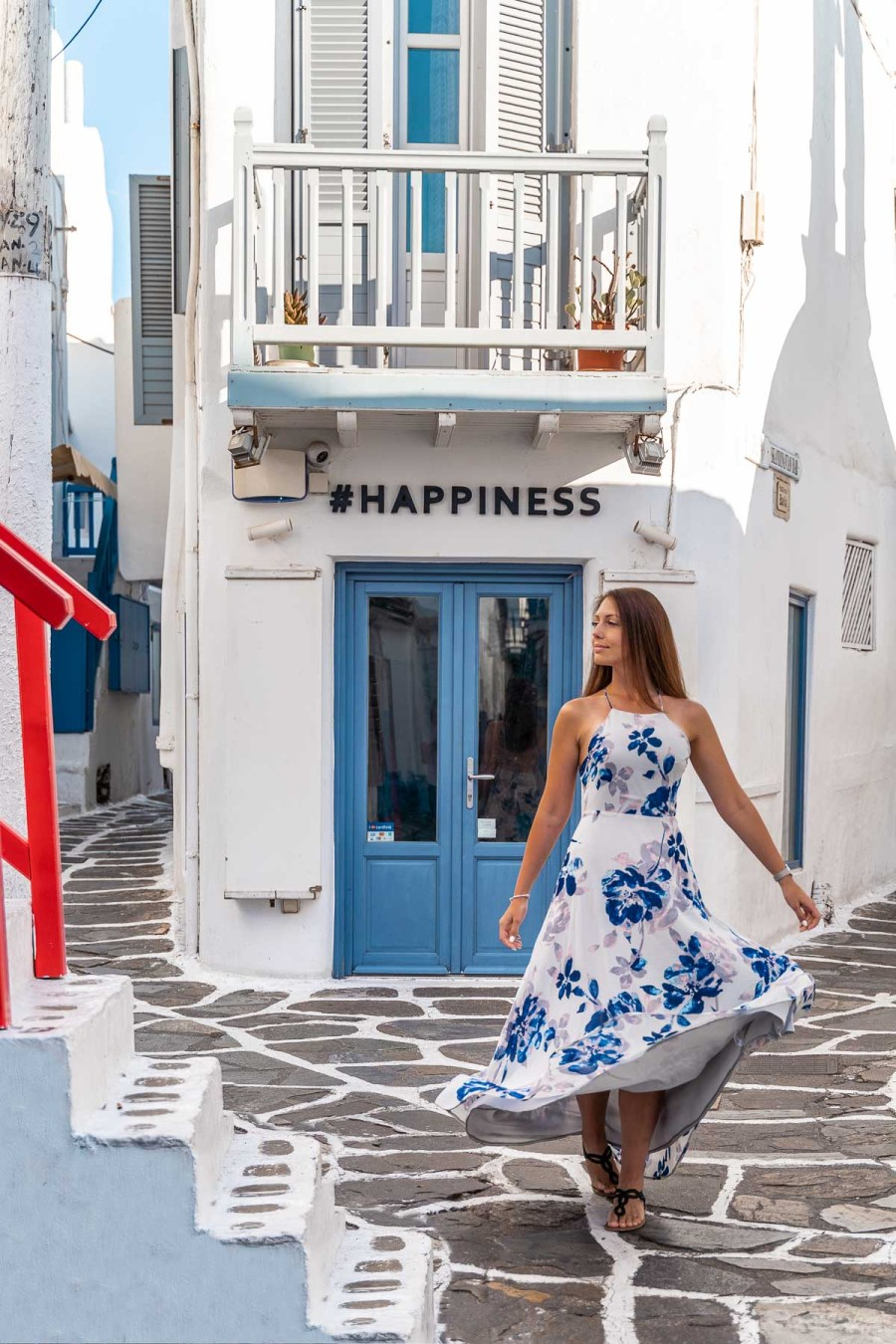 Girl in a blue floral dress twirling in front of the #happiness store which is one of the most instagrammable places in Mykonos