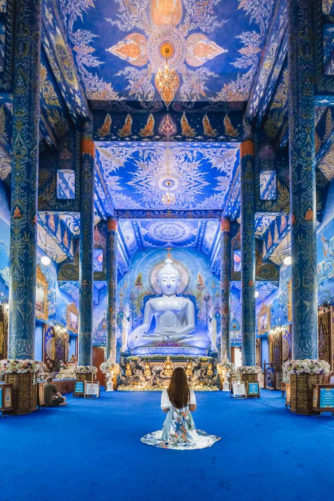 Girl in a blue dress sitting in front of a white Buddha statue in the Blue Temple in Chiang Rai