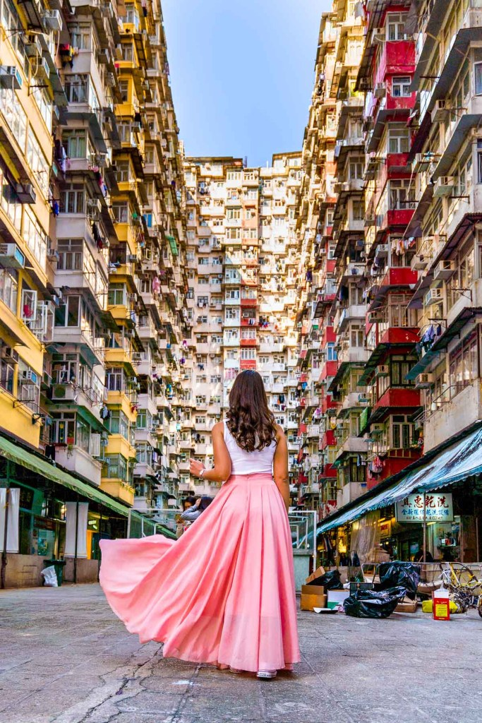 Girl in a pink skirt standing in front of Fok Cheok Building, aka the Monster building in Hong Kong