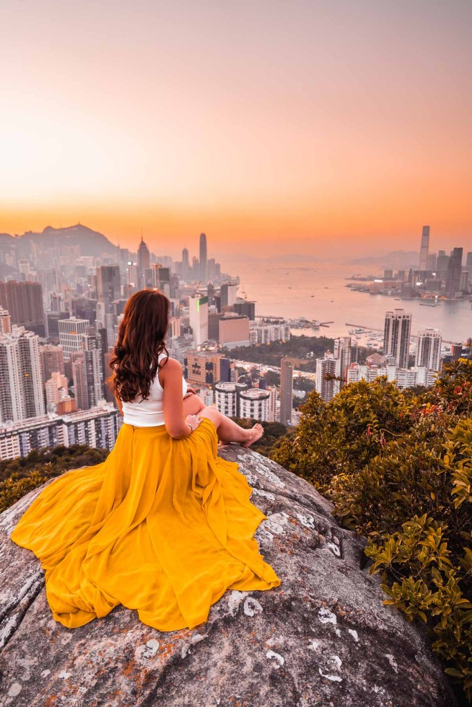 Girl in a yellow skirt sitting on a rock, watching the sunset from Braemer Hill, Hong Kong
