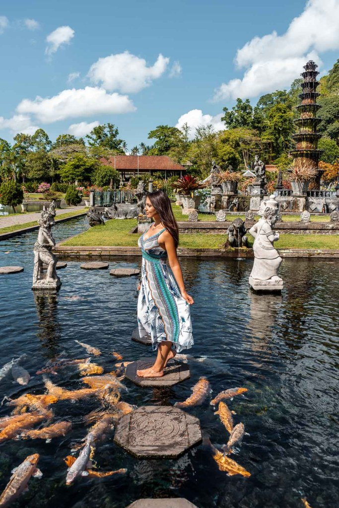 Girl in a blue-white dress standing in the middle of the pool at Tirta Gangga Royal Water Garden in Bali