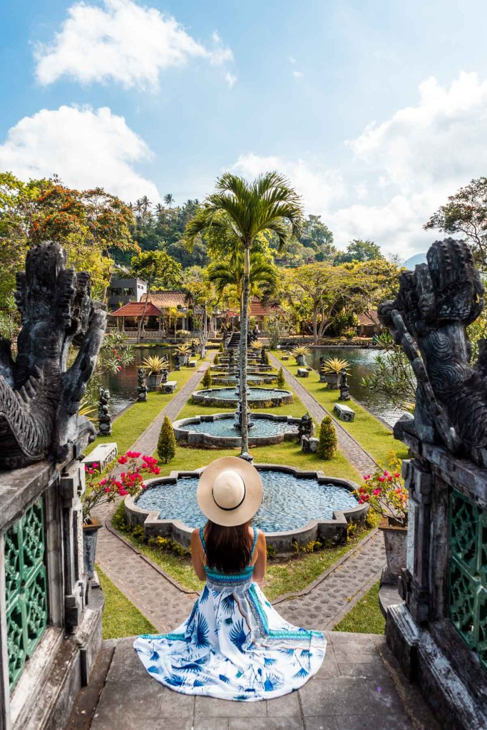 Girl in a blue-white dress sitting on the stairs at Tirta Gangga Royal Water Garden in Bali