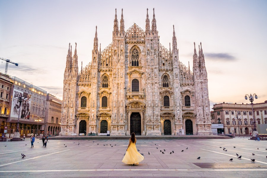 Girl in a yellow dress twirling in front of the Duomo di Milano in Italy