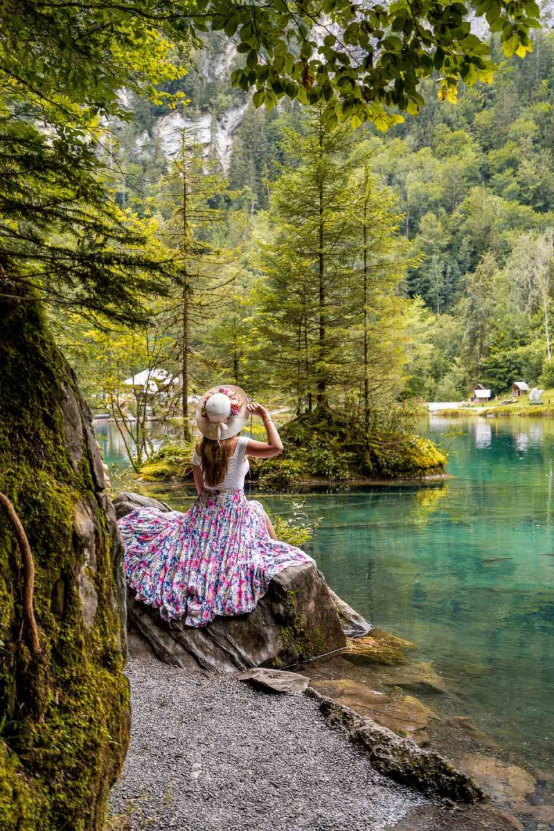 Girl in a purple skirt sitting on a rock at Blausee, Switzerland