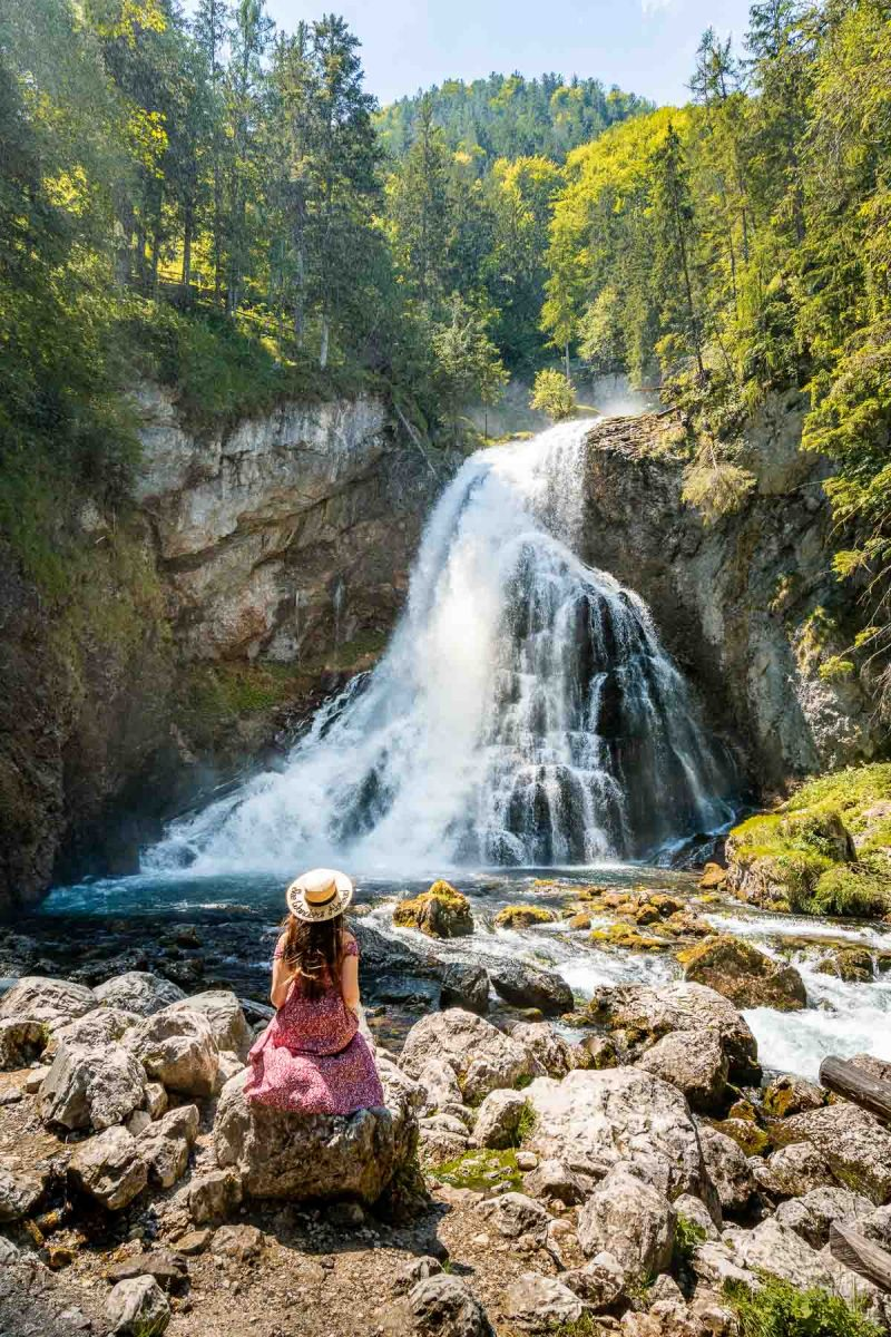 Girl in a red dress sitting in front of Gollinger waterfall, Austria