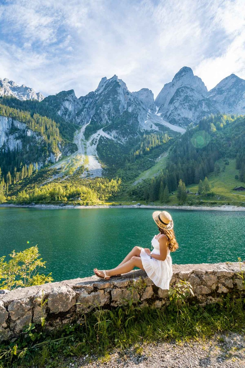 Girl in a white dress sitting on the shores of Gosauseen, Austria
