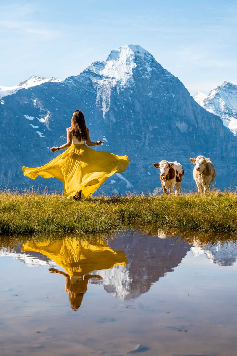 Girl in a yellow dress looking at the mountain panorama at Grindelwald First in Switzerland