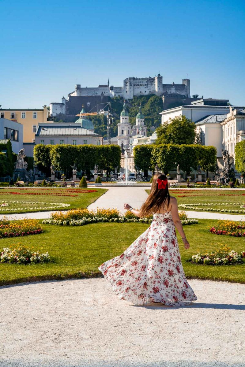Girl in a floral dress twirling in Mirabell Gardens, Salzburg
