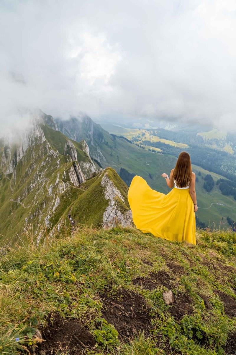 Girl in a yellow skirt in front of Schaeffler Ridge, Ebenalp, Switzerland