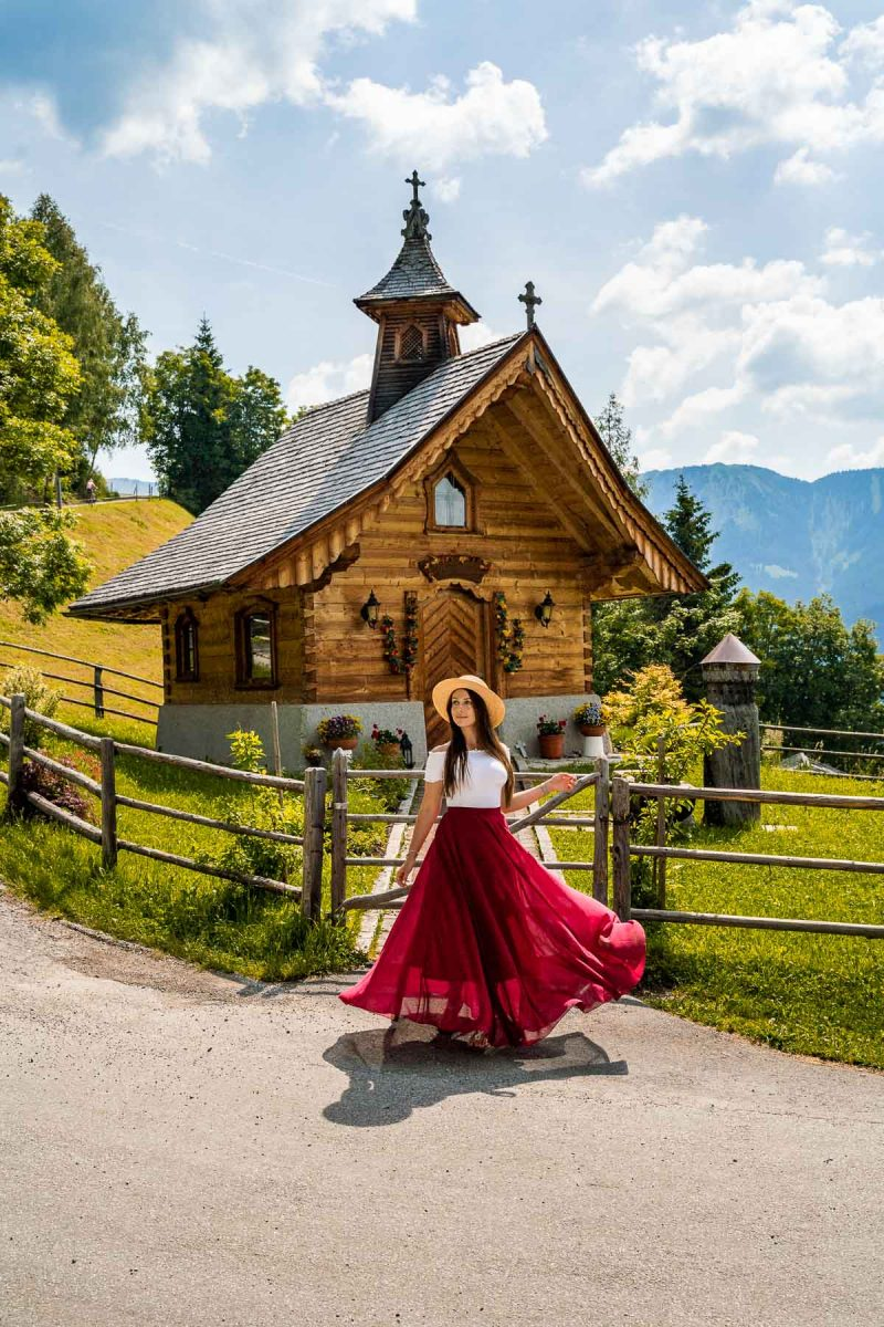 Girl in a red skirt in front of a tiny chapel at Mitterberghof Jausenstation, Austria