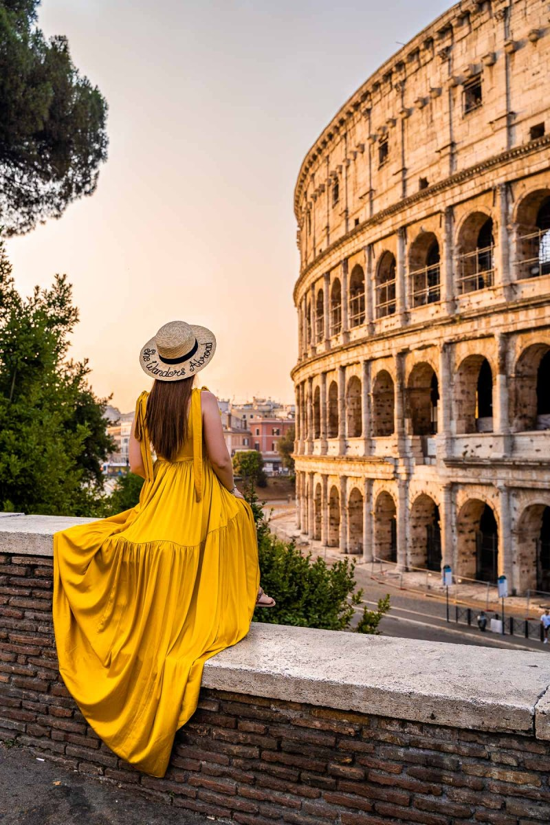 At Sunrise girl in a yellow dress at the Colosseum in Rome, Italy