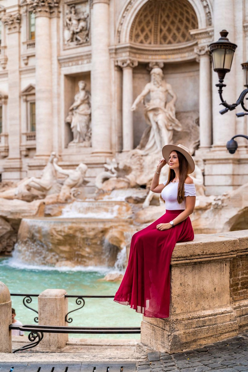 Girl in a red skirt in front of the Trevi Fountain in Rome, Italy