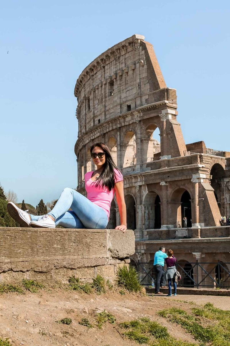 Girl in a pink skirt sitting in front of the Colosseum in Rome, Italy