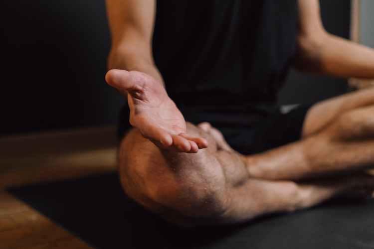 man practicing meditation on sports mat