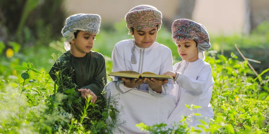 Трое оманских мальчишек в национальных одеждах читают Коран на природе
