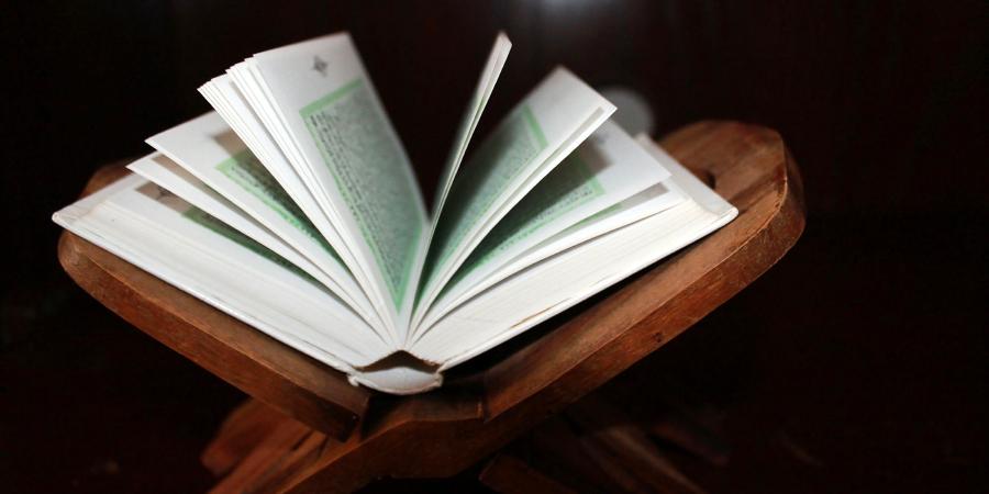 Открытый Коран на деревянной подставке