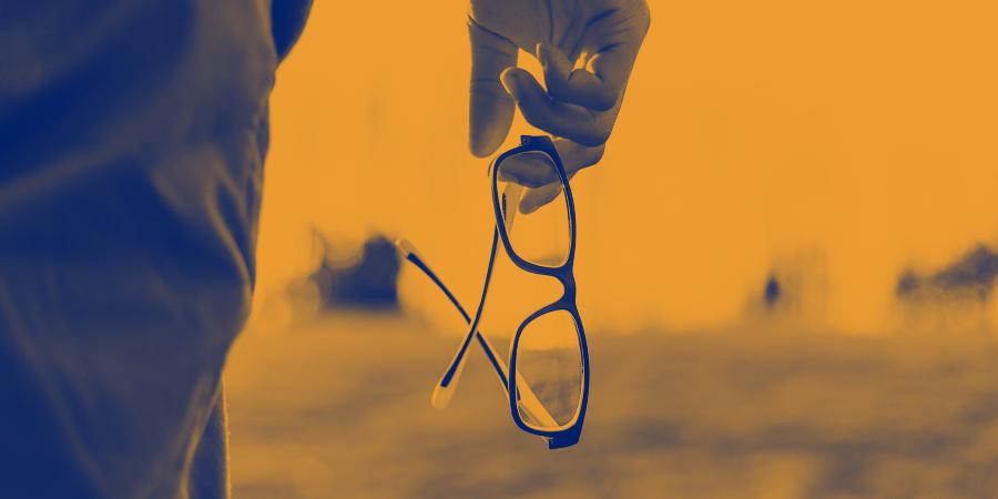 Человек, держащий в руке очки
