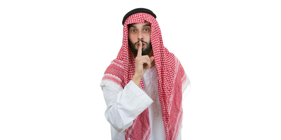 Араб в национальной одежде призывает к молчанию