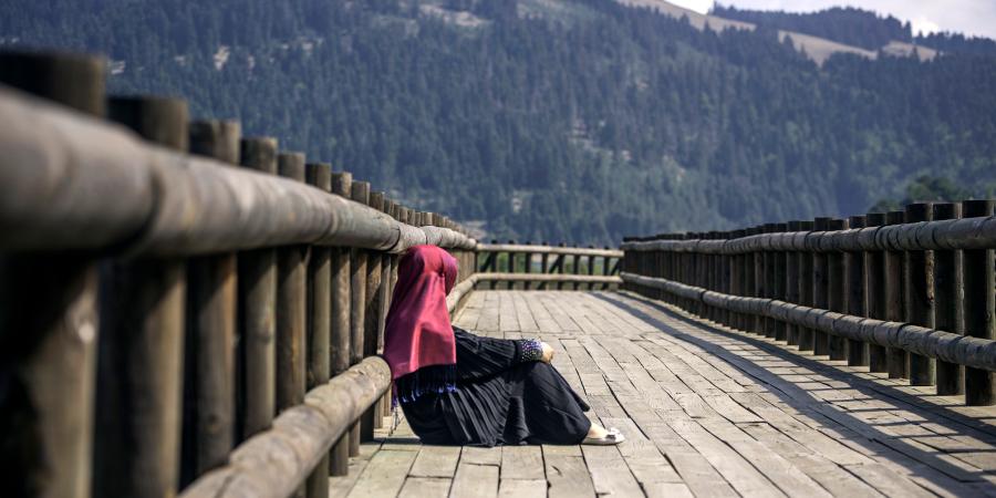 Мусульманка, сидящая на деревянном мосту