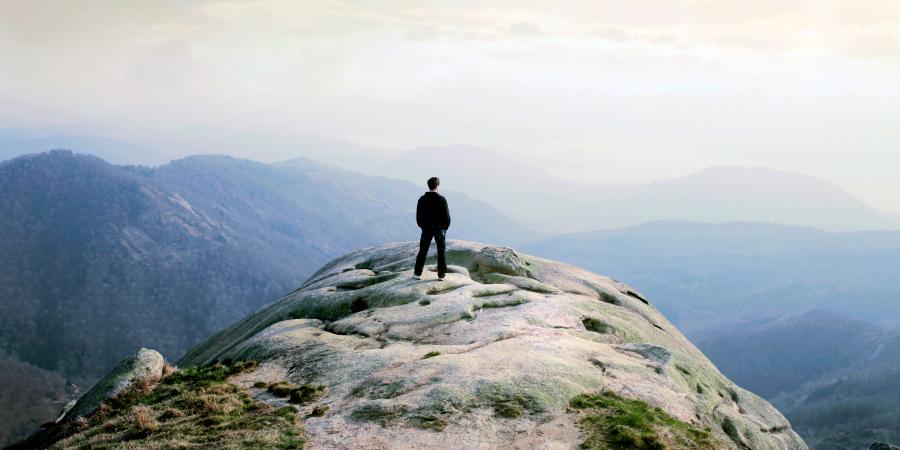 Мужчина, стоящий на вершине горы