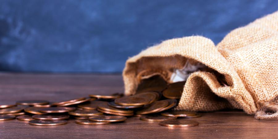 Мешочек с монетами на деревянном столе