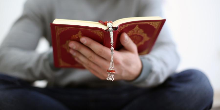 Молодой человек, читающий красный Коран
