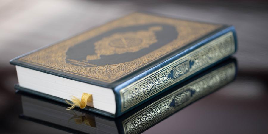 Священный Коран на зеркальной поверхности