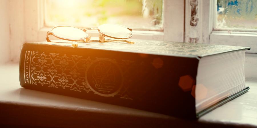 Коран с очками возле окна