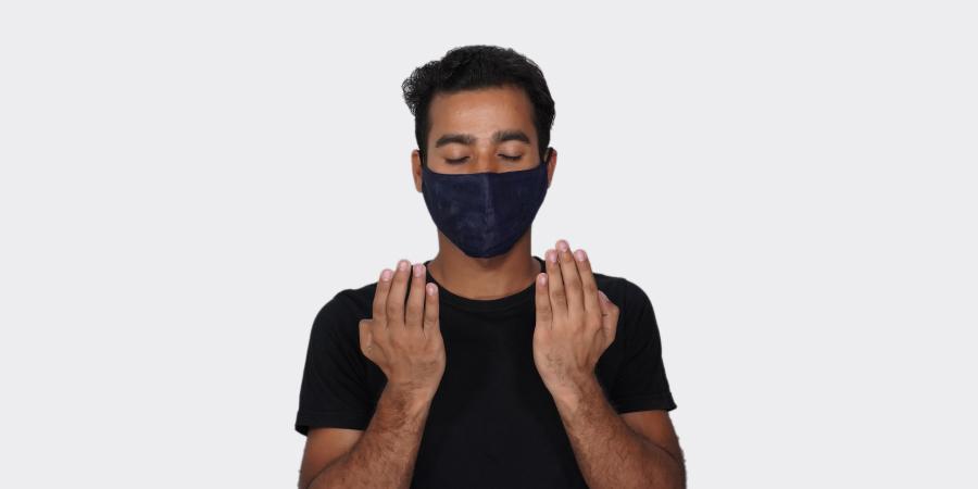 Мужчина в медицинской маске, читающий дуа