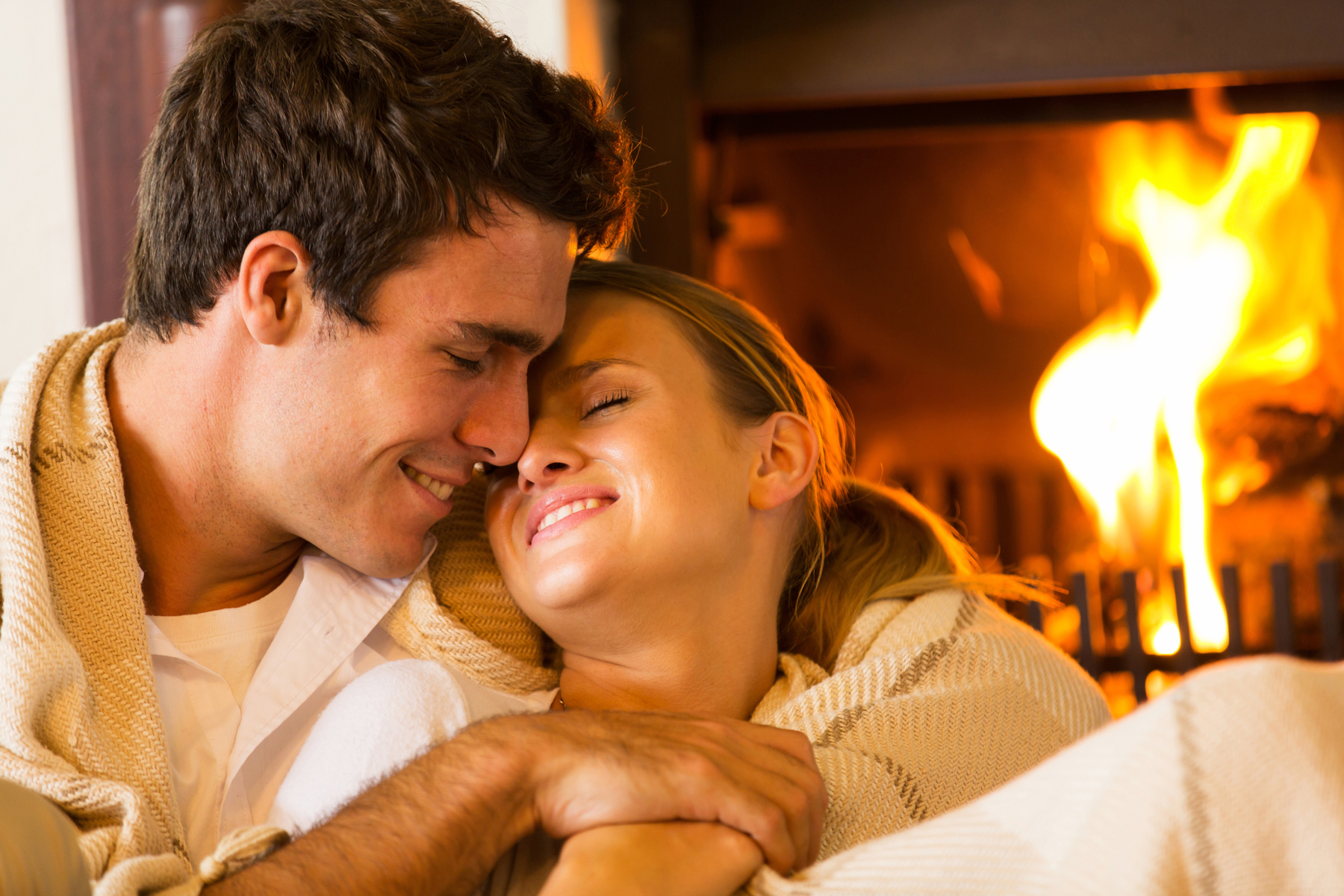 couple cuddling in front of fireplace