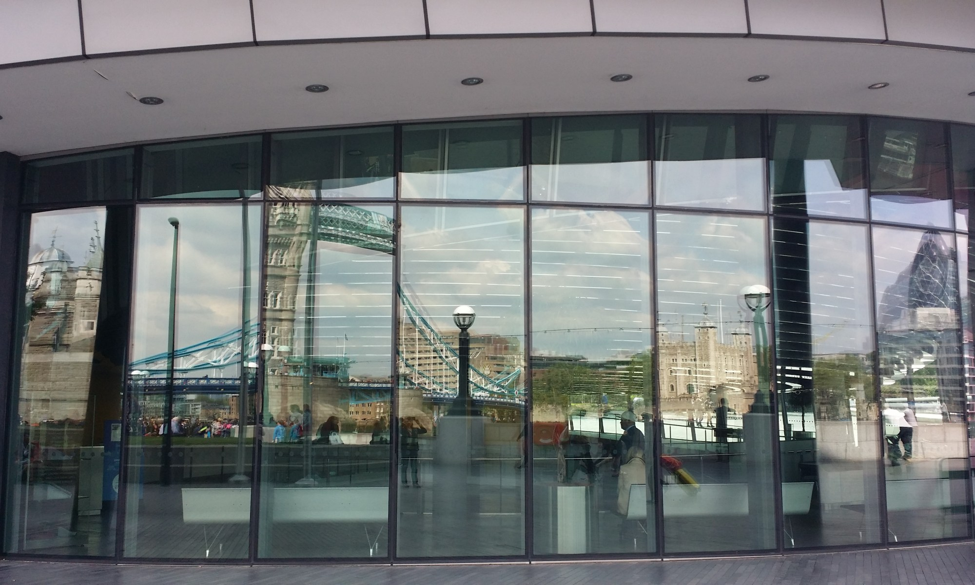 in the windows of a London building, reflections from across the Thames of Tower Bridge and other landmarks