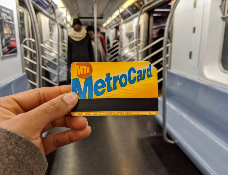 Holding a MetroCard on a NYC train - top NYC subway pet peeves
