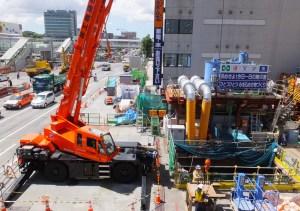延期報道があった8月25日も炎天下のなかで建設工事はいつものように進められていた(新横浜駅前)