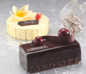 """今年の新ケーキ2品は「例年と異なり、""""大人の雰囲気""""落ち着いたケーキに仕上げました」とのこと。光沢のあるショコラで包まれた「エトワール」、ホワイトチョコムースにレモンクリームと苺のジュレを合わせたという「ペルスネージュ」(奥)(同ホテル提供)"""