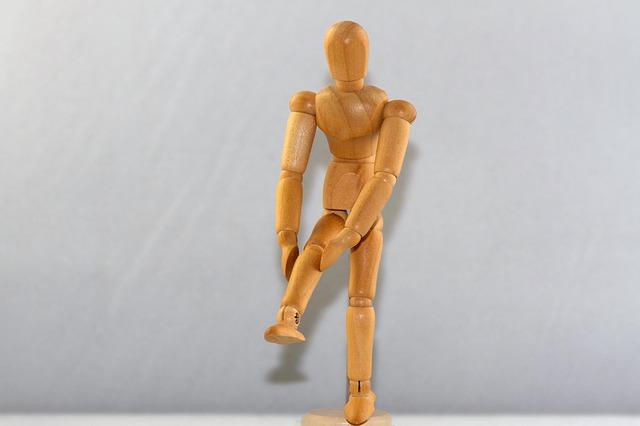 膝を抑える人形