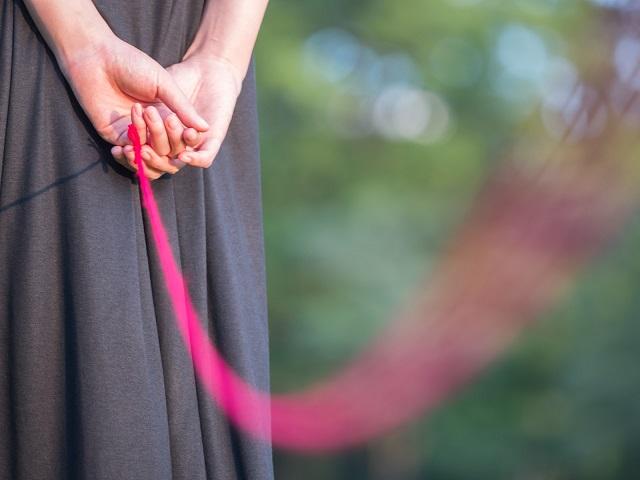 女性の指に繋がった赤い糸