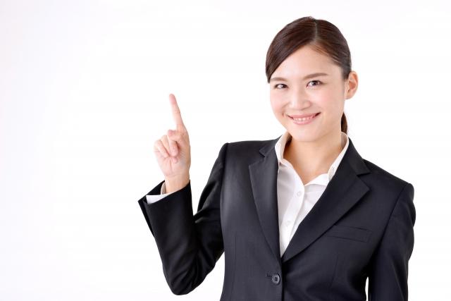 指を立てたスーツ姿の女性