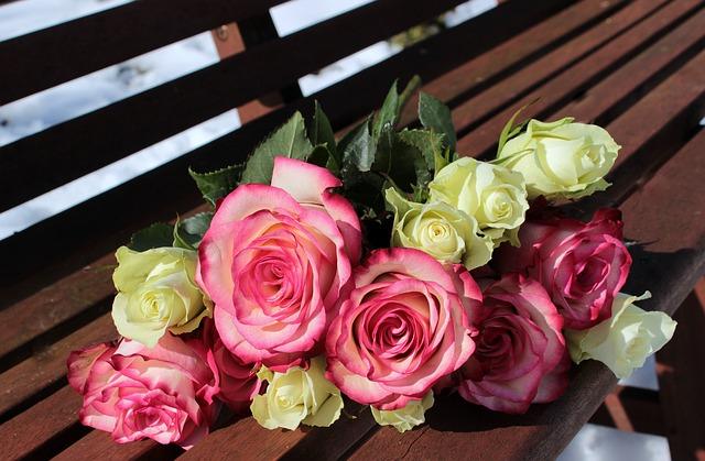 ベンチに置かれたピンクと白のバラの花