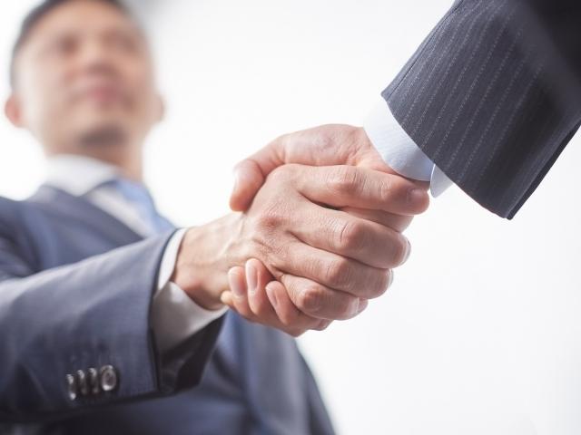 スーツ姿の男性が握手する様子