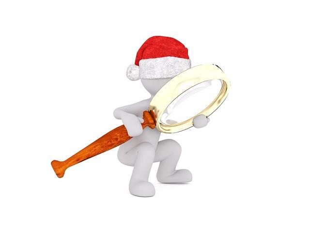 サンタの帽子をかぶった人が虫眼鏡を見る
