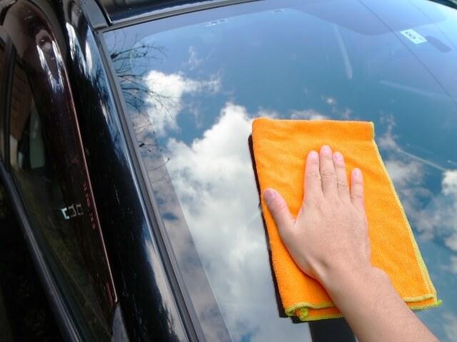 車の窓を拭く手